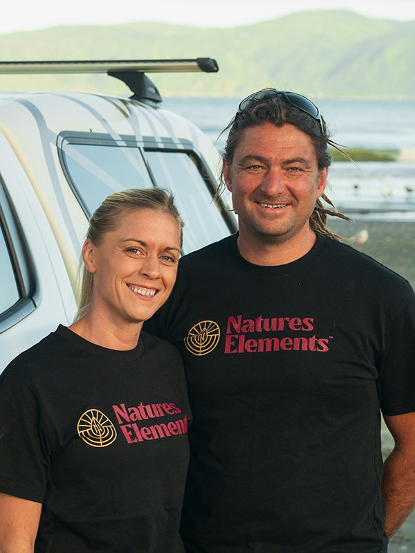 Marty and Marie Boyland from Natures Elements Landscaping standing on Paraparaumu Beach with Kāpiti Island in the background