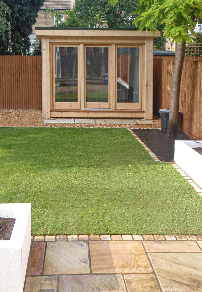 A shed in the back yard of a home with artificial grass and paving Kapiti